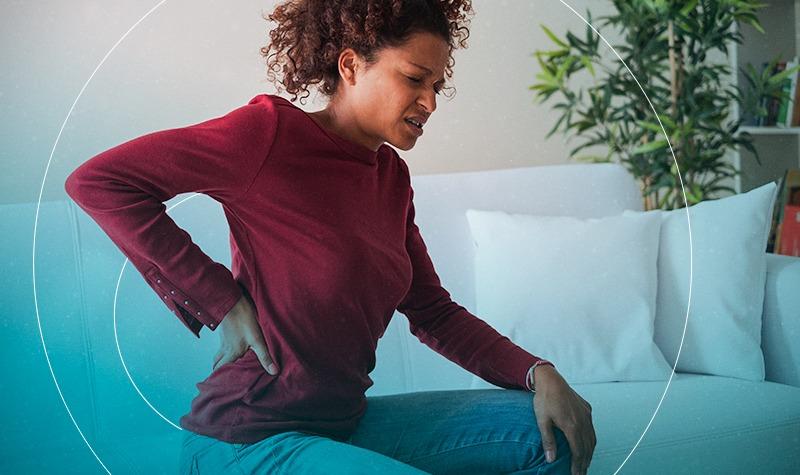 Quais são os sintomas associados à dor lombar?